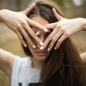woman covering face wearing white nail polish