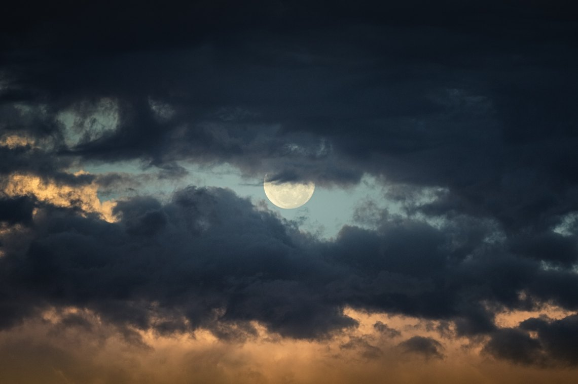 The moon peaking out behind clouds