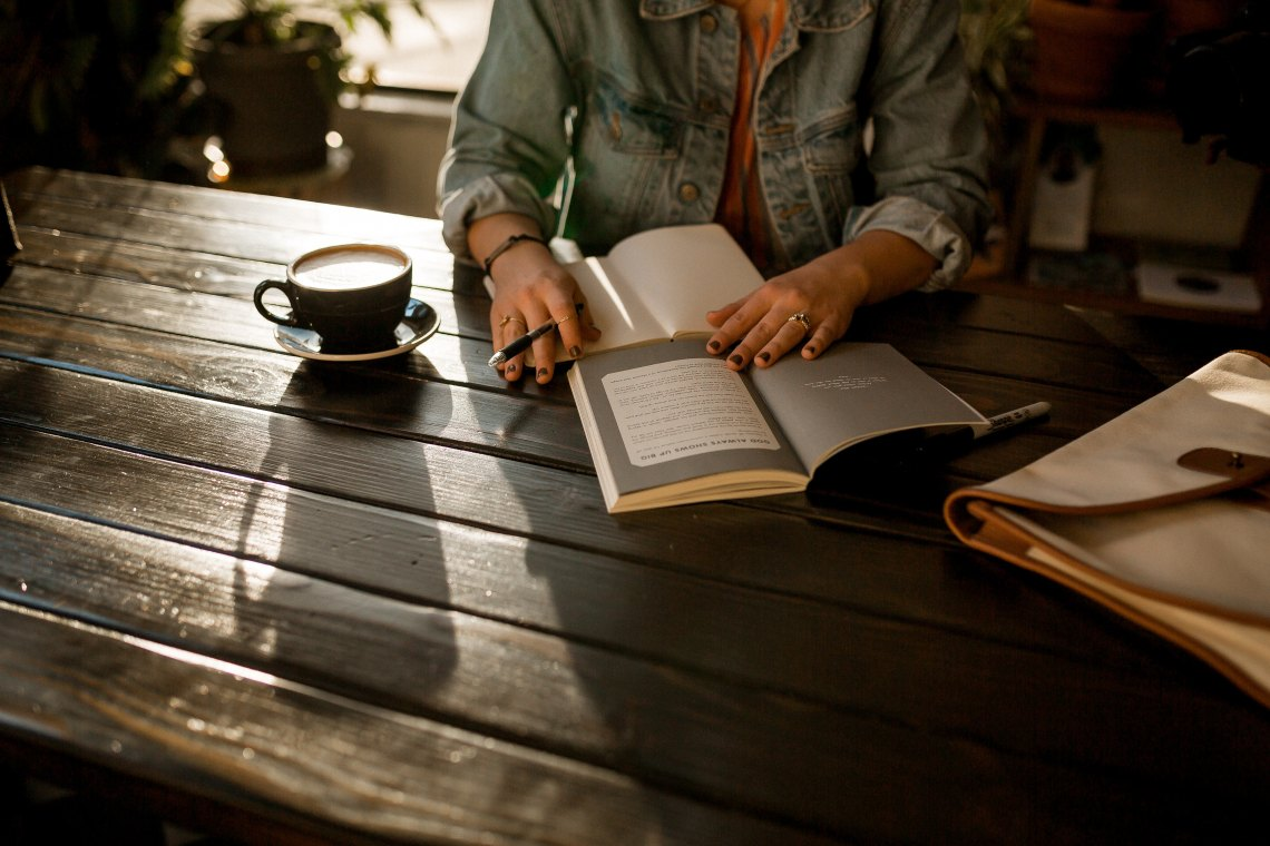 a writer sits at a table with coffee and her notebook