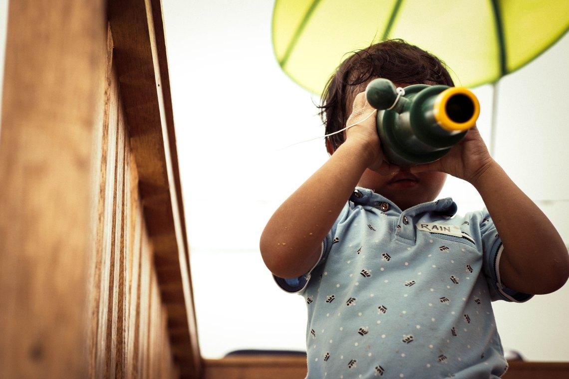 A little kid looks through a telescope