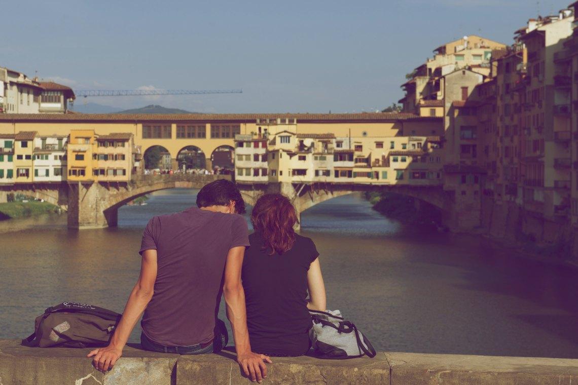 couple sitting on bridge together
