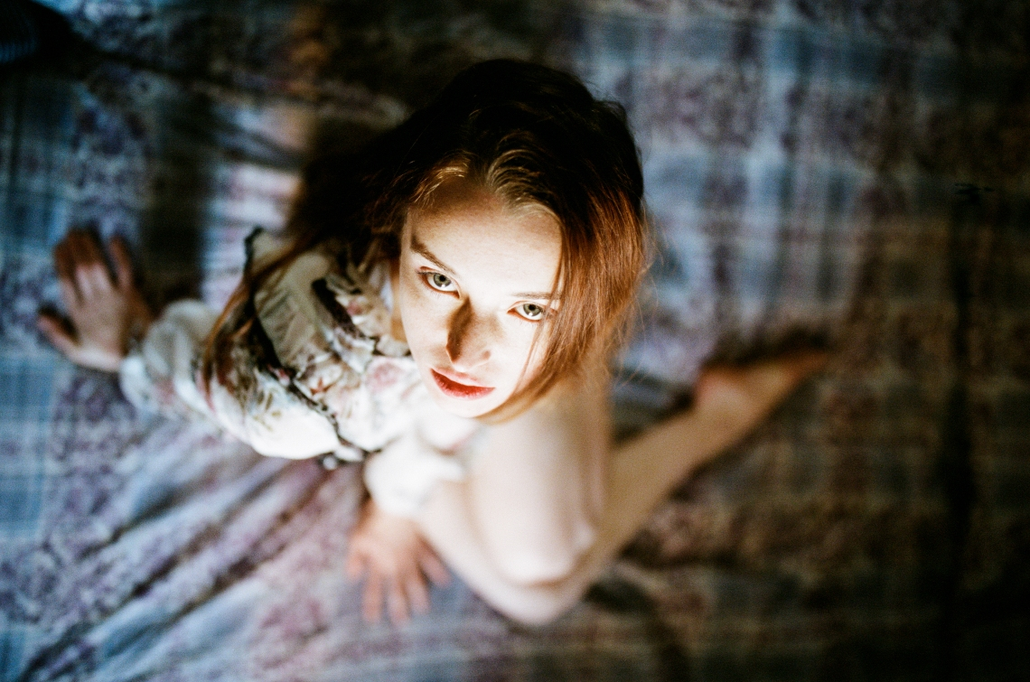 intense woman sitting on bed