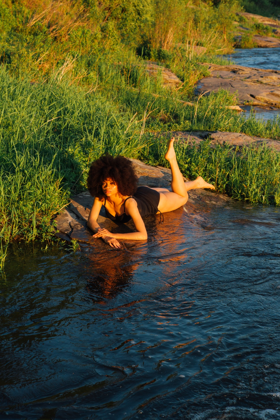 woman laying down in bathing suit by water
