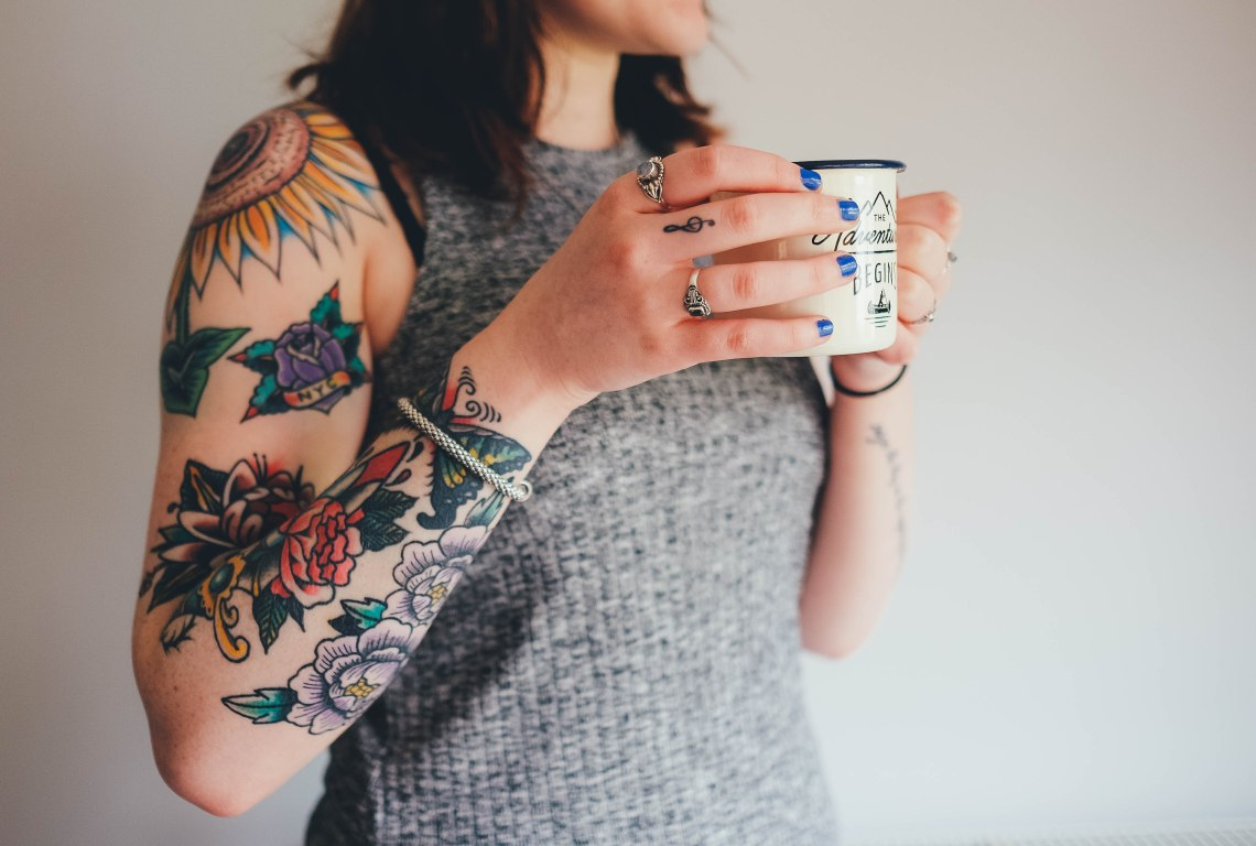 woman with tattoos holding coffee cup