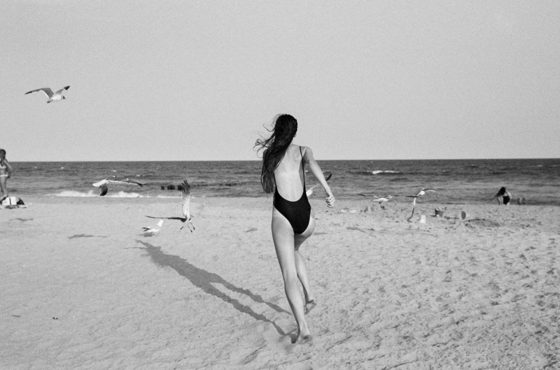 woman happily running on beach