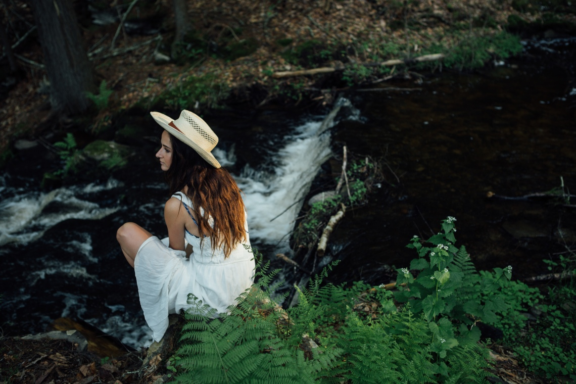 woman sitting along creek