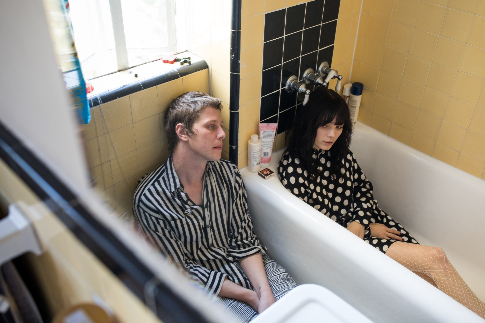 couple sitting in bathroom looking bored