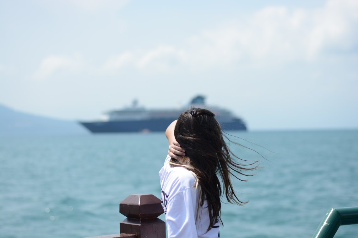 woman standing along shoreline holding hair