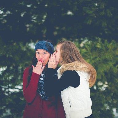 Friends whisper secrets in each other's ears