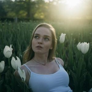 woman looking hopeful in tulips