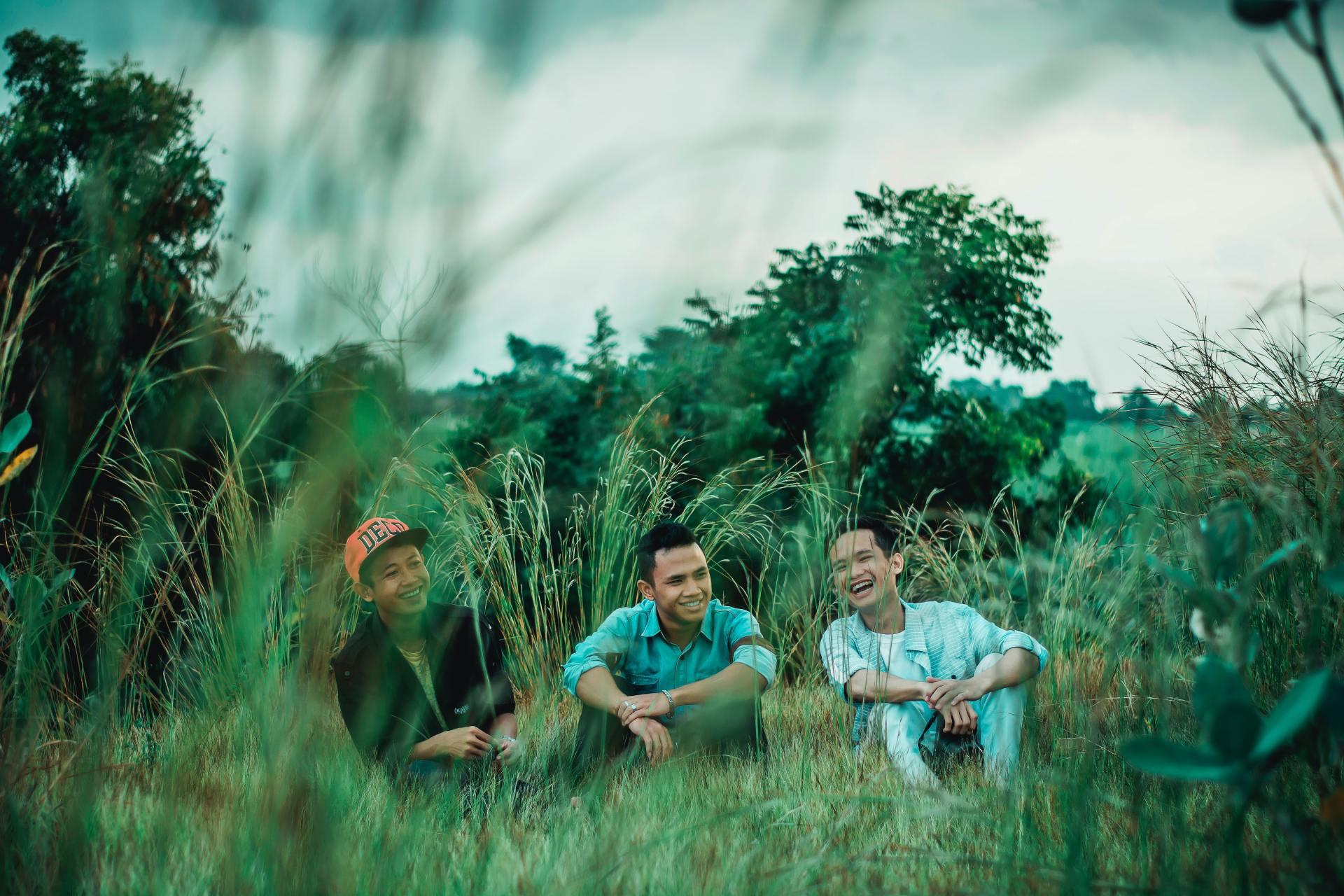 Photo of Men Sitting on Grass