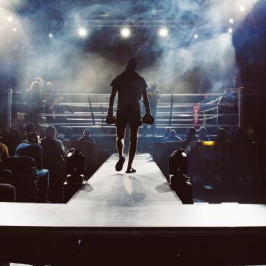man standing and walking going on boxing ring surrounded with people photo