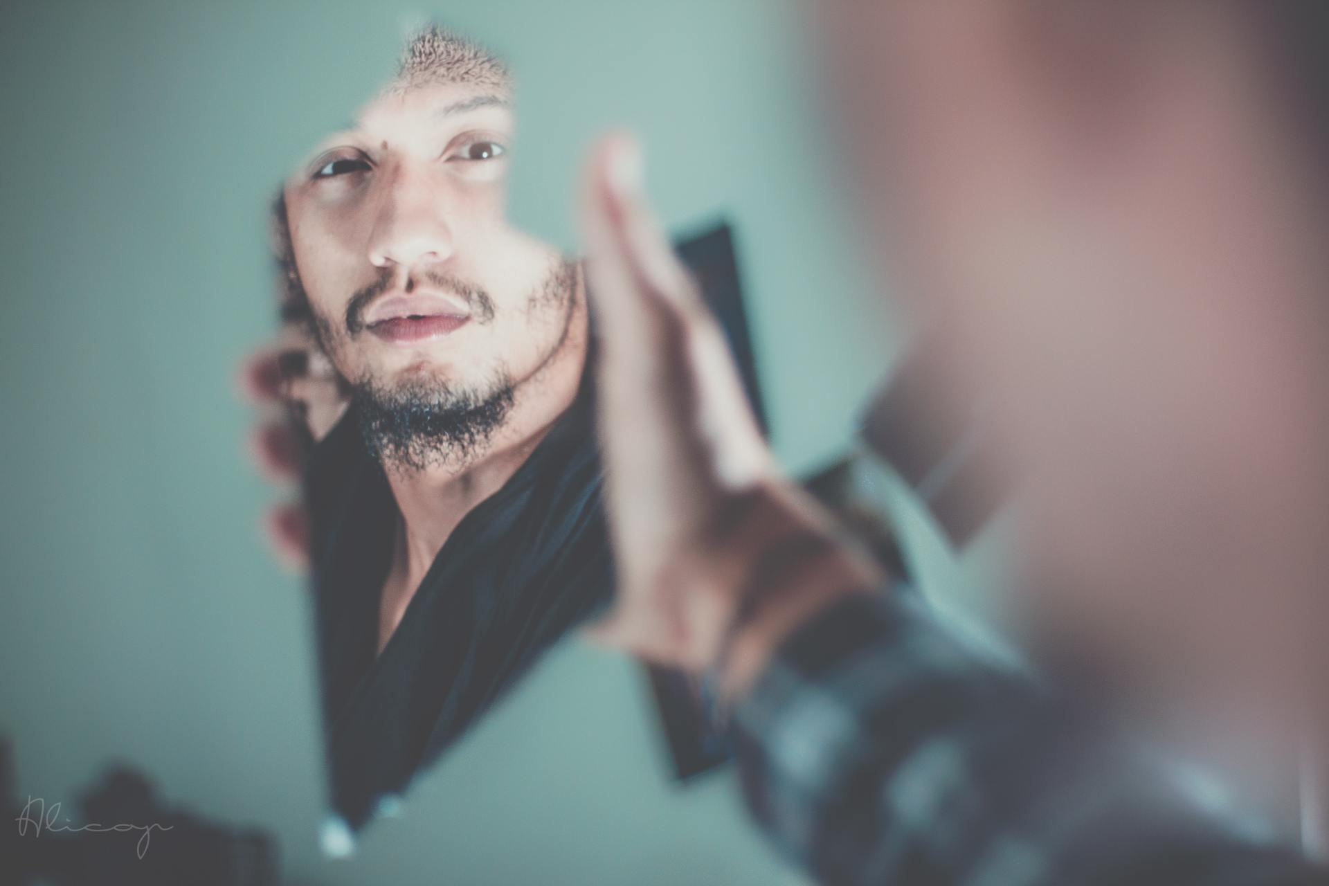 selective focus photography of man's reflection in broken mirror