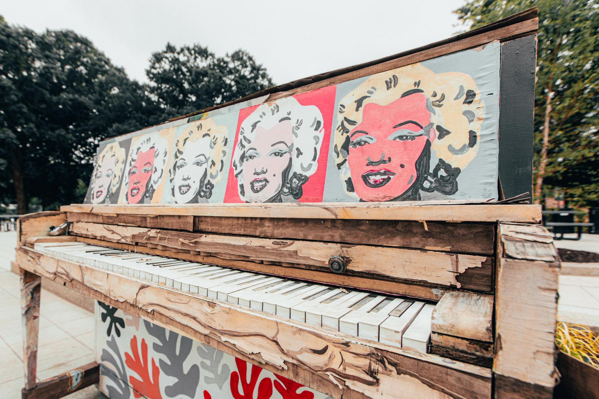 Red and white graffiti on brown wooden fence