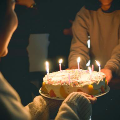 Two People Holding Cake With Lit Candles