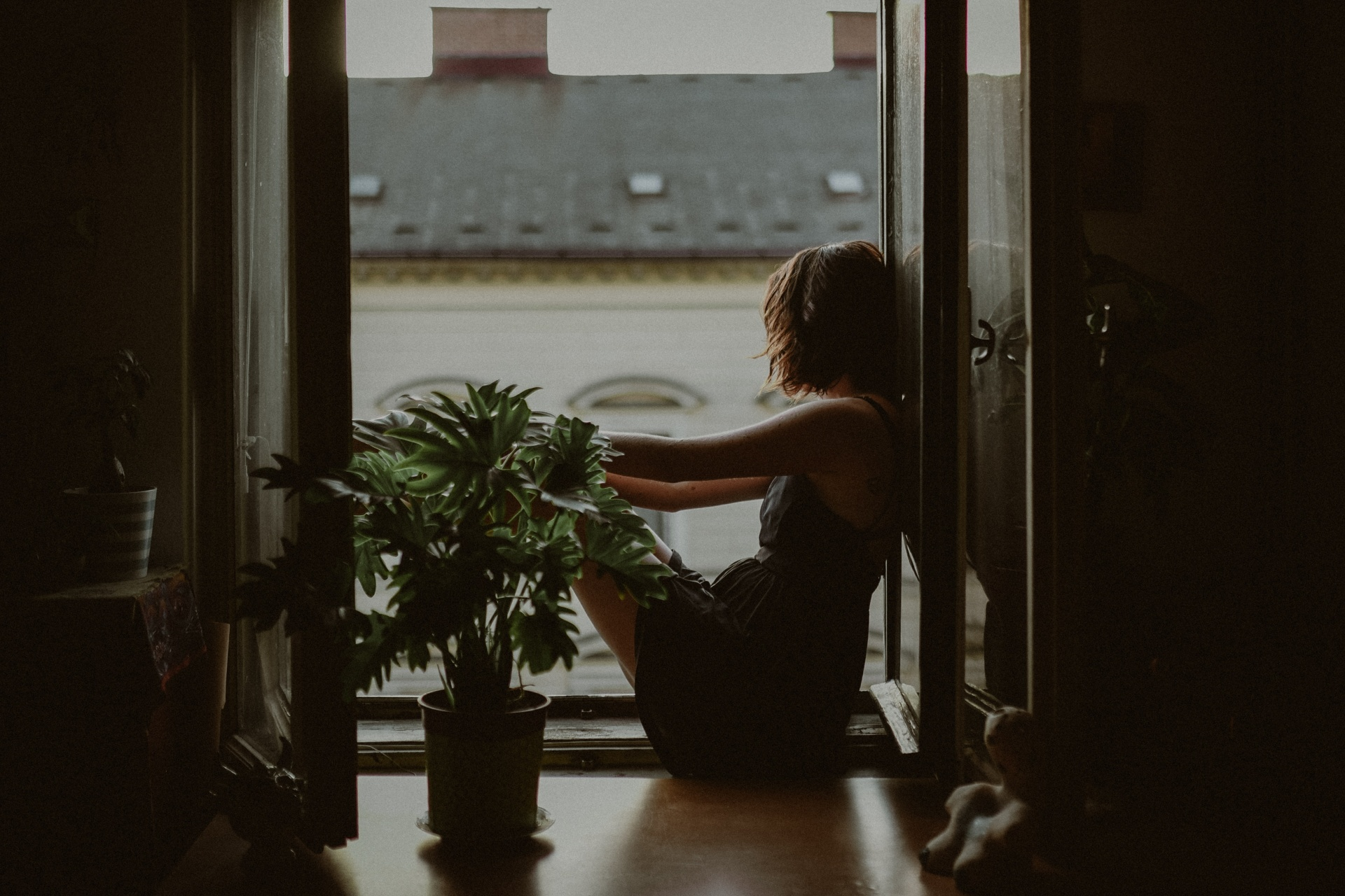 Woman leaning on door looking outside photo