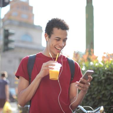Cheerful man with smartphone drinking juice on street