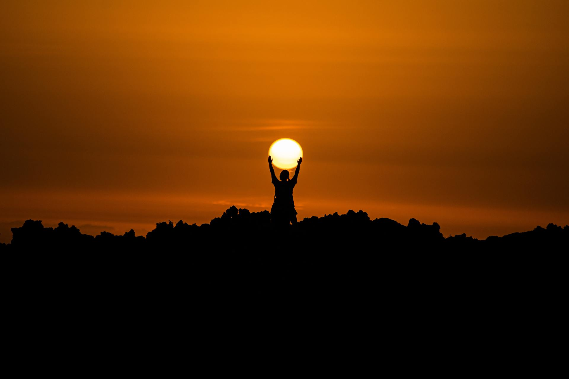 silhouette of person holding sun